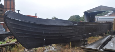 Black painted narrowboat hull mounted on blocks on dry land