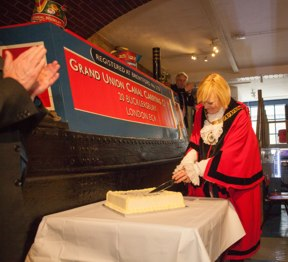 Mayor in scarlet robes cuts cake in front of Coronis narrowboat